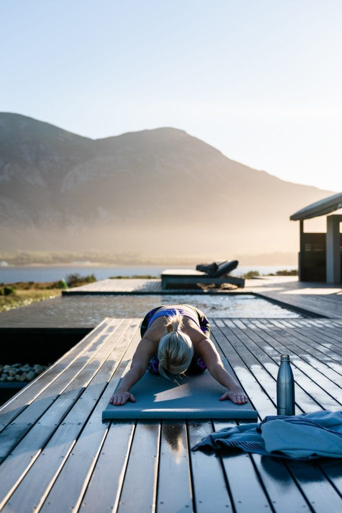 A guest doing yoga on the deck at Perivoli Lagoon House